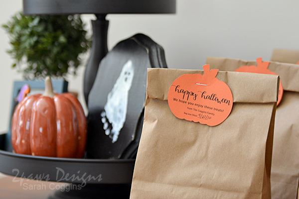 View of pumpkin label on Halloween treat bags with tiered seasonal display in background.