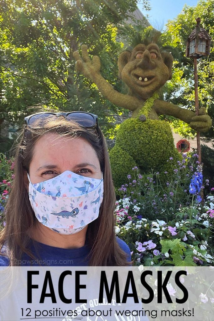 Woman wearing Frozen 2 themed face mask in front of Troll topiary at Epcot.