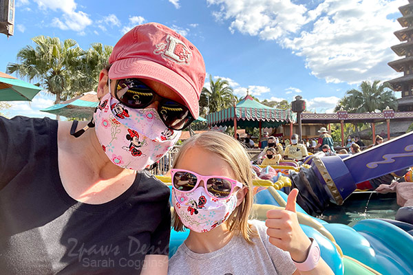 Mother and daughter wearing matching Minnie Mouse face masks on Magic Carpets of Aladdin ride.