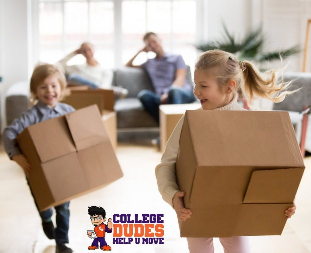 Boy and Girl Children carrying moving boxes while parents sit on sofa in background watching.